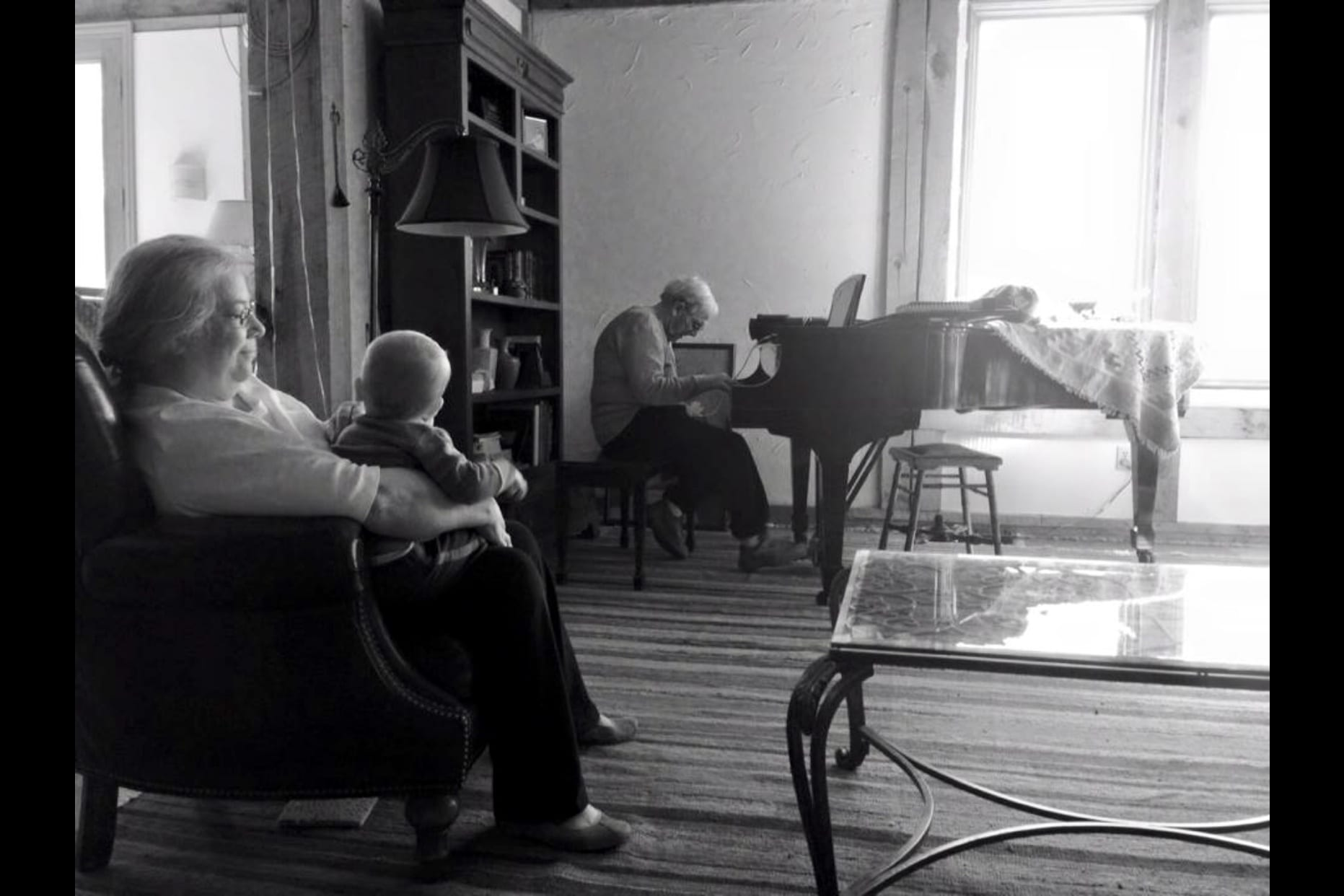 Ron playing piano and wife and grandchild listening